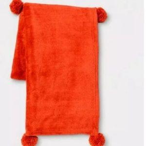 Neon orange pompom throw blanket